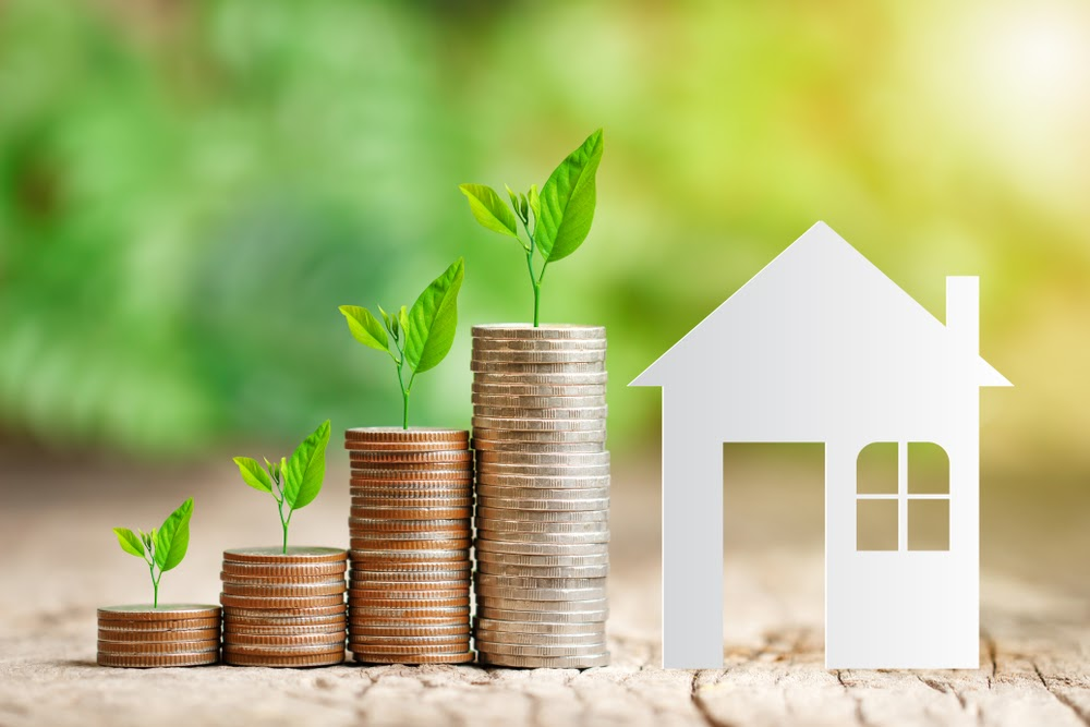 House paper model and tree growing on coins stack for saving to buy a house